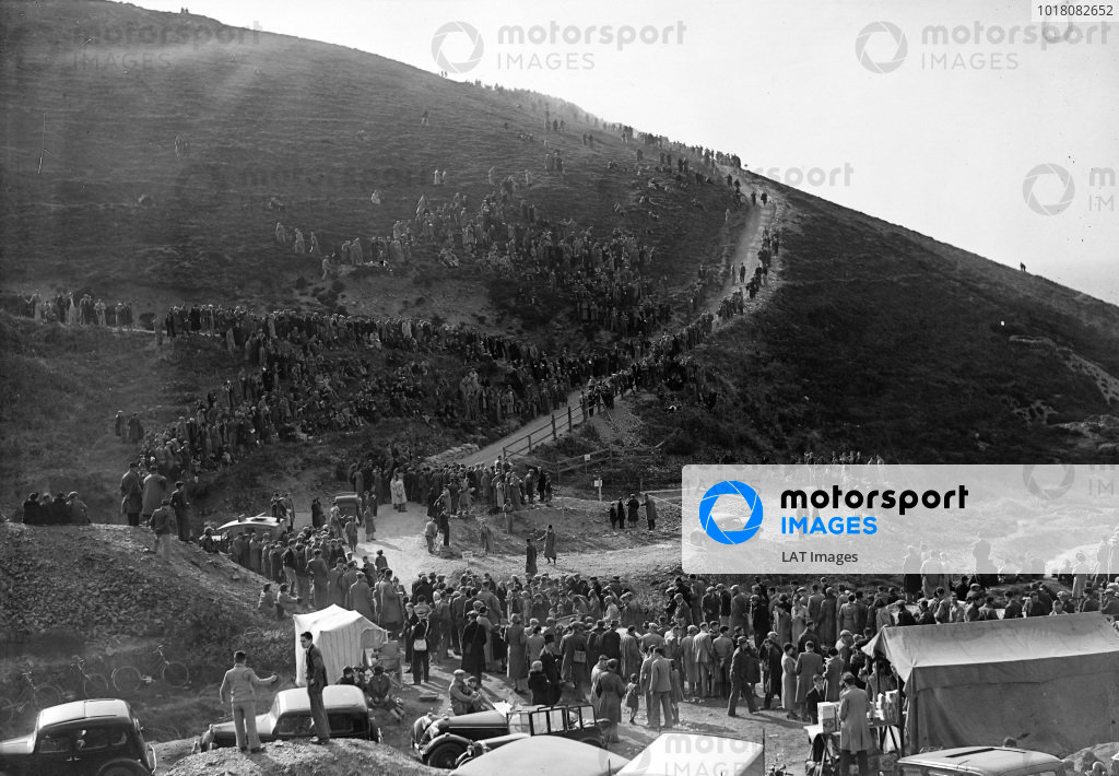 Spectators crowd along the route of the course as it winds its way up a hill in order to watch the cars in action.