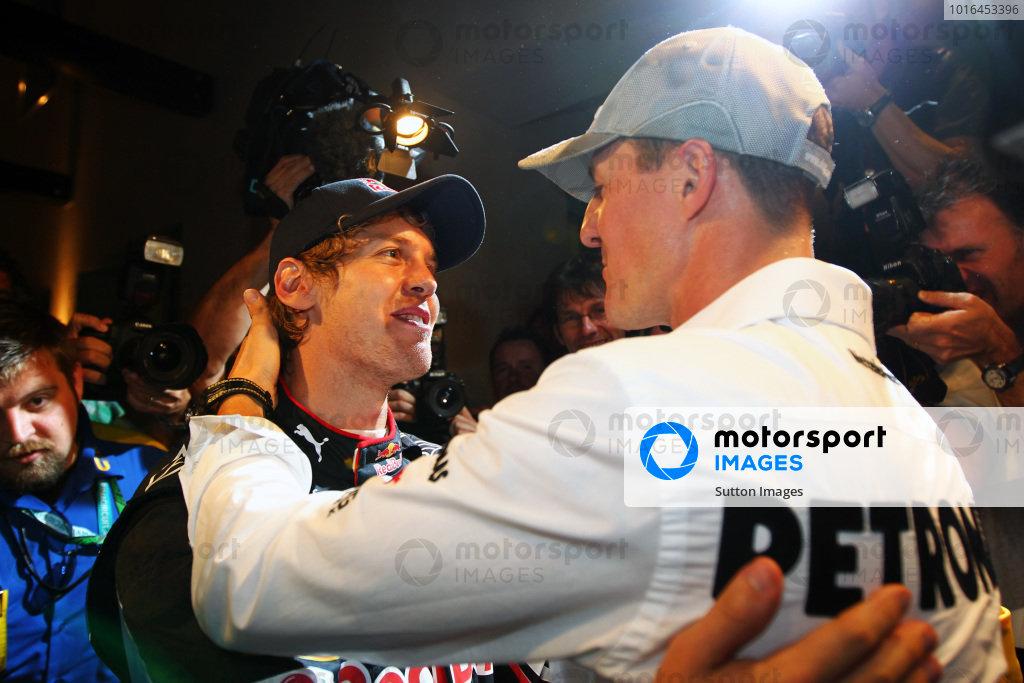 Michael Schumacher (GER) Mercedes GP congratulates 2010 World Champion Sebastian Vettel (GER) Red Bull Racing. Formula One World Championship, Rd 19, Abu Dhabi Grand Prix, Race, Yas Marina Circuit, Abu Dhabi, UAE, Sunday 14 November 2010.  BEST IMAGE