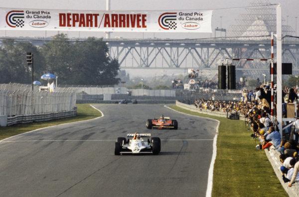 Alan Jones, Williams FW07 Ford celebrates victory as he crosses the finish line ahead of Gilles Villeneuve, Ferrari 312T4.