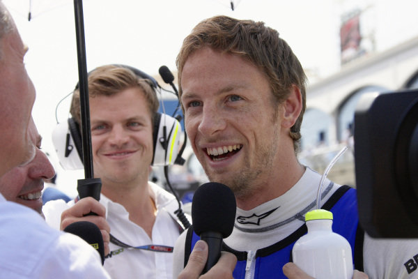 Jenson Button gives an interview on the grid.