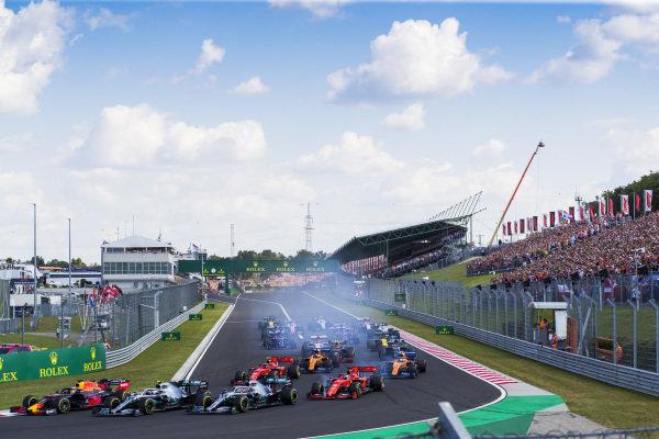 Max Verstappen, Red Bull Racing RB15, leads Valtteri Bottas, Mercedes AMG W10, Lewis Hamilton, Mercedes AMG F1 W10, Charles Leclerc, Ferrari SF90, Carlos Sainz Jr., McLaren MCL34, Sebastian Vettel, Ferrari SF90, and the rest of the field at the start