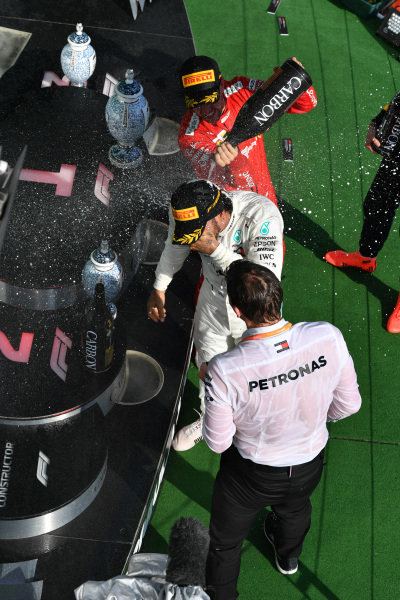Sebastian Vettel, Ferrari, 3rd position, blasts Lewis Hamilton, Mercedes AMG F1, 1st position, with Champagne on the podium