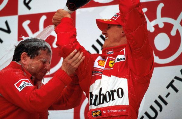 Suzuka, Japan.6-8 October 2000.Michael Schumacher (Ferrari) celebrates with Ferrari Team Principal Jean Todt on the podium, after winning the Grand Prix and the drivers World Championship. World copyright - LAT Photographic