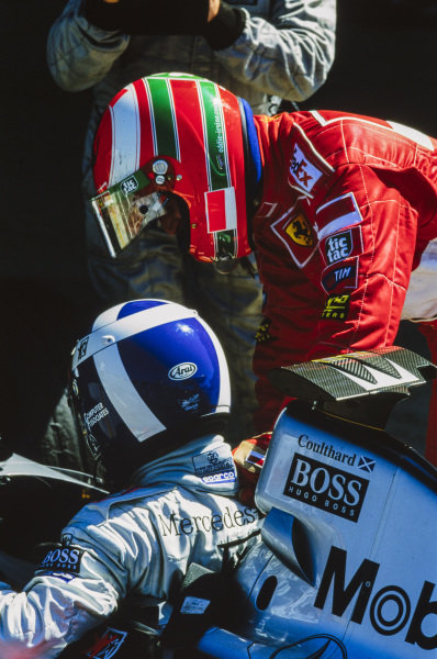 Eddie Irvine, 2nd position, congratulates David Coulthard,1st position, in Parc Ferme.