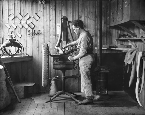 A wounded New Zealand soldier repairs a tyre in the vulcanising shop of the Oatlands Park Hospital, Weybridge.