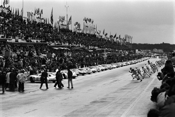 Drivers run to their cars at the start.