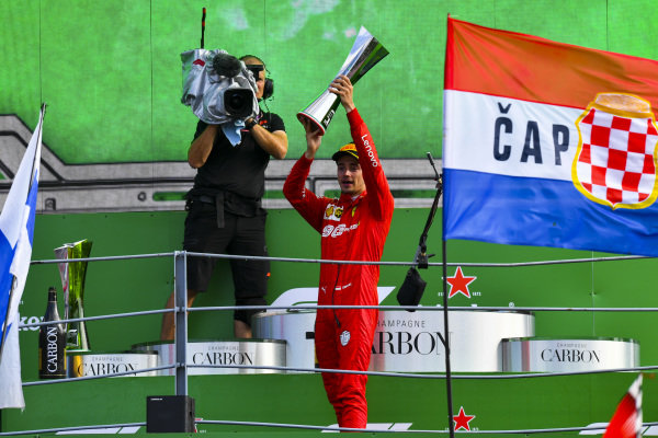 Charles Leclerc, Ferrari, 1st position, lifts the winners trophy