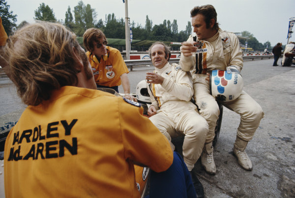 Denny Hulme and Peter Revson, with Alistair Caldwell and mechanic Dave Luff in the McLaren pit.