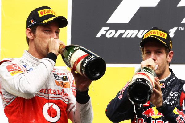 Jenson Button (GBR) McLaren and Sebastian Vettel (GER) Red Bull Racing on the podium.  Formula One World Championship, Rd 12, Belgian Grand Prix, Race, Spa-Francorchamps, Belgium, Sunday 28 August 2011.  BEST IMAGE