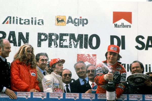 Imola, Italy. 23rd - 25th April 1982. Didier Pironi (Ferrari 126C2), 1st position, sprays Champagne as a dejected Gilles Villeneuve (Ferrari 126C2), 2nd position, looks on, podium, portrait.  World Copyright: LAT Photographic. Ref:  82SM08.