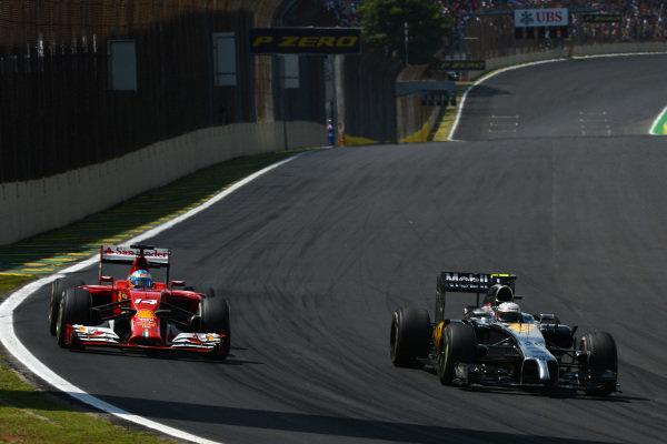(L to R): Fernando Alonso (ESP) Ferrari F14 T and Kevin Magnussen (DEN) McLaren MP4-29. Formula One World Championship, Rd18, Brazilian Grand Prix, Race, Sao Paulo, Brazil, Sunday 9 November 2014.