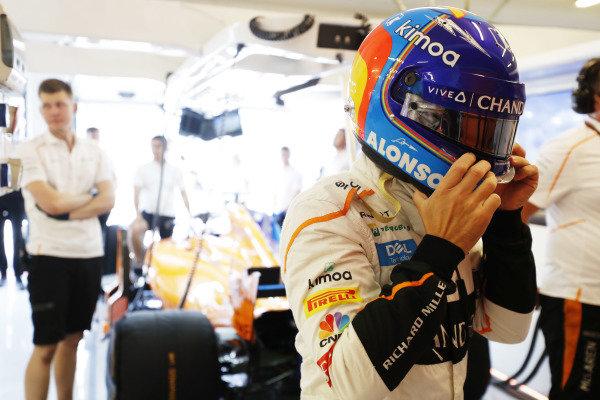 Fernando Alonso, McLaren, puts on his helmet in the garage.