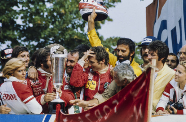 Winner Clay Regazzoni embraces Emerson Fittipaldi, 2nd position, and teammate Niki Lauda, 3rd position, on the podium.