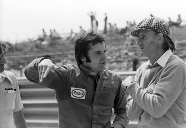 (L to R): Alan Jones (AUS), who finished thirteenth in his first race with the Hill team, talks with the Hill team owner Graham Hill (GBR).Dutch Grand Prix, Rd 8, Zandvoort, Holland, 22 June 1975.
