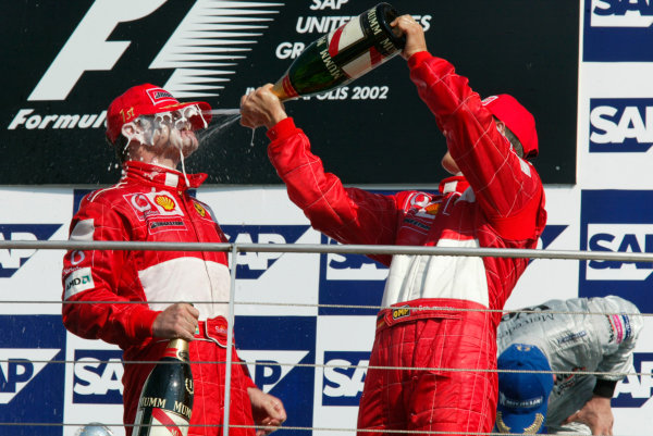 2002 American Grand Prix.Indianapolis, Indiana, USA. 27-29 September 2002.Michael Schumacher (Ferrari) 2nd position and Rubens Barrichello (Ferrari) 1st position celebrate with champagne on the podium.World Copyright - LAT Photographicref: Digital File Only
