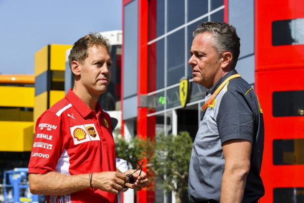 Sebastian Vettel, Ferrari an Mario Isola, Racing Manager, Pirelli Motorsport talk in the paddock