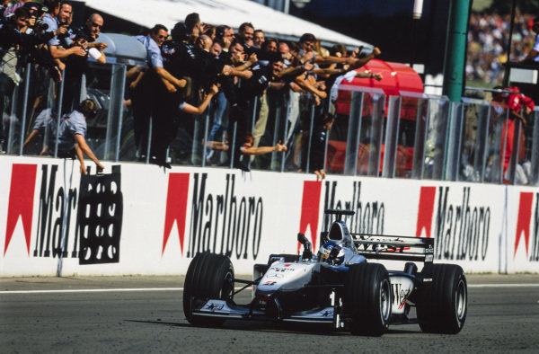 Mika Häkkinen, McLaren MP4-15 Mercedes, crosses the line for victory to the delight of the McLaren team watching from the pit wall.