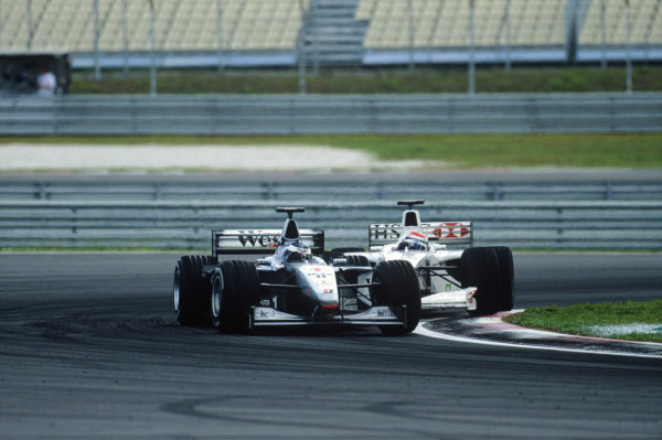 Sepang, Kuala Lumpur, Malaysia. 15-17 October 1999. Mika Hakkinen (McLaren MP4/14 Mercedes) leads Johnny Herbert (Stewart SF-3 Ford). Action. Ref: 99MAL12. World Copyright - LAT Photographic