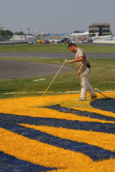 2003 Champ Car Series 22-24 August 2003Molson Indy Montreal Circuit Gilles Villeneuve.Montreal, Quebec, Canada. Track worker finishes painting grass signs in turn 2. 2003- Dan R. Boyd USA LAT Photography