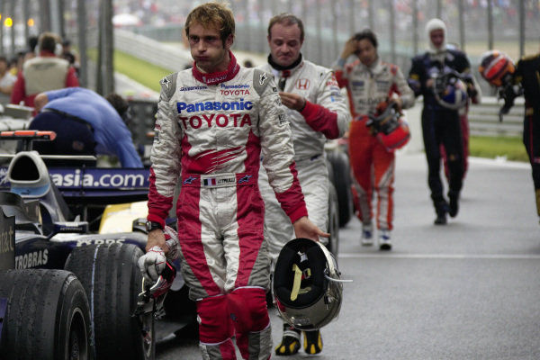 After the race, Jarno Trulli and Rubens Barrichello walk back from scrutineer parking.