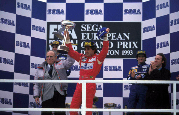 Ayrton Senna, 1st position, with the trophy on the podium.  Tom Wheatcroft is on the left of frame standing just in front of Damon Hill, 2nd position, with Alain Prost, 3rd position, on the right.