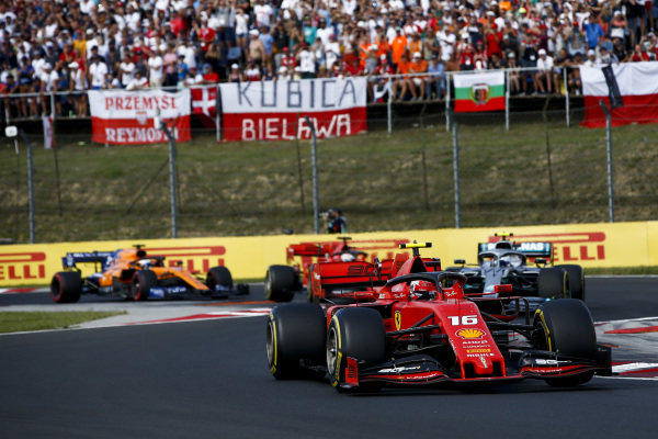 Charles Leclerc, Ferrari SF90, leads Valtteri Bottas, Mercedes AMG W10, Sebastian Vettel, Ferrari SF90, and Carlos Sainz Jr., McLaren MCL34