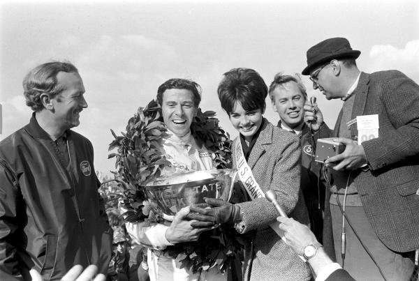L to R: Colin Chapman, Lotus team owner; Jim Clark (GBR) Lotus 49 celebrating another victory; Miss US Grand Prix; Keith Duckworth - designer of the Cosworth DFV that powered the Lotus to victory - being interviewed. Formula One World Championship, US GP, Watkins Glen, 1 Oct 1967