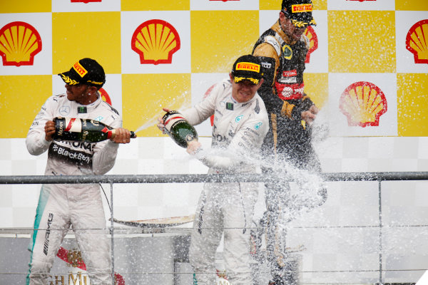 Spa-Francorchamps, Spa, Belgium. Sunday 23 August 2015. Lewis Hamilton, Mercedes AMG, 1st Position, Nico Rosberg, Mercedes AMG, 2nd Position, and Romain Grosjean, Lotus F1, 3rd Position, spray Champagne on the podium. World Copyright: Alastair Staley/LAT Photographic ref: Digital Image _79P5561