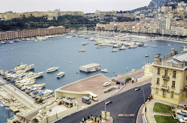 Cars fly past the Monaco harbour.