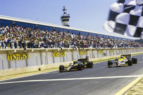 Ayrton Senna, Lotus 98T Renault, leads Nigel Mansell, Williams FW11 Honda, across the line and takes the chequered flag.