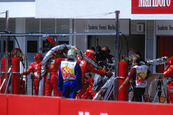 2004 Hungarian Grand Prix Hungaroring, Hungary. 13th - 15th August. THe Ferrari team trying to fix one of their re-fueling rigs during the race.World Copyright:Steven Tee/LAT Photographi--c Ref:35mm Image:A13