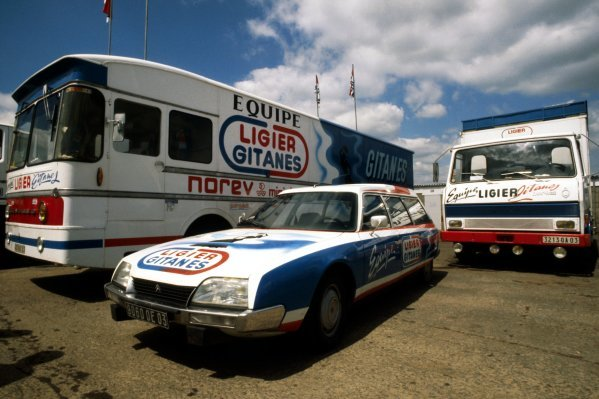 The Ligier entourage, including a Citroen CX and the team transporter, sit in the Silverstone paddock.