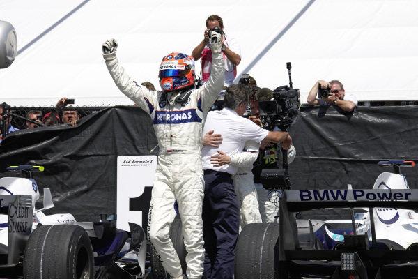 Robert Kubica celebrates victory in parc ferme as Dr Mario Theissen hugs Nick Heidfeld in the background.