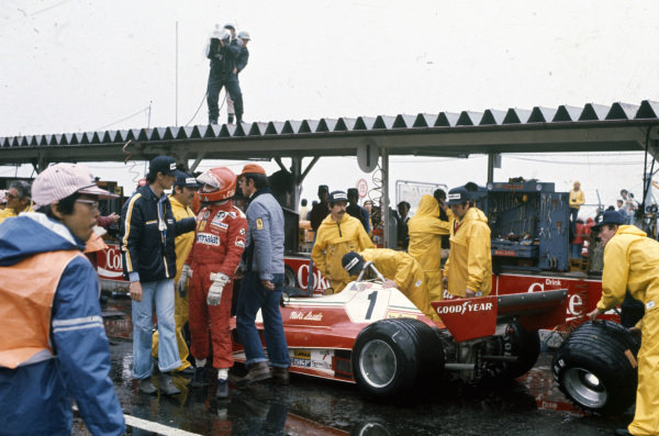 Niki Lauda speaking with Daniele Audetto as he withdraws from the race under the bad weather conditions.