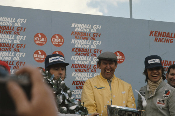 Jackie Stewart celebrates victory on the podium with teammate Francois Cevert, 2nd position, and team boss Ken Tyrrell.