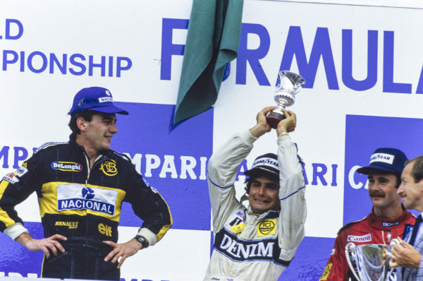 Nelson Piquet, 1st position, jokes around on the podium alongside Ayrton Senna, 2nd position, and Nigel Mansell, 3rd position.