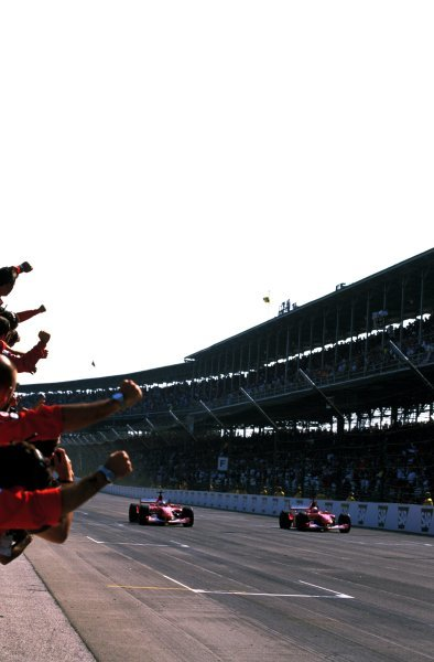 Race leader Michael Schumacher (GER), right, and Rubens Barrichello (BRA), left, slowed down to take a Ferrari formation finish at Indy. Barrichello took the chequered flag from Schumacher by 0.01 of a second causing more controversy for the team.