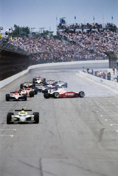 Tony Renna, Kelley Racing, Dallara IR-03 Toyota, leads the pack while Scott Dixon, Ganassi Racing, G-Force GF05 Toyota, spins.