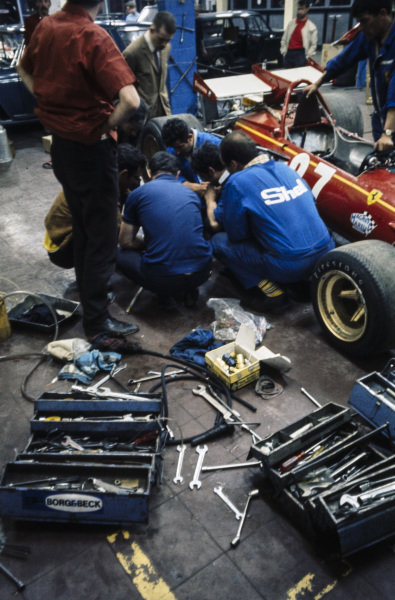 Mechanics work on Jacky Ickx's, Ferrari 312B in the garage.