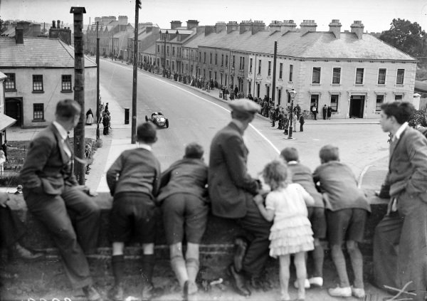 Fans watch the action from the railway bridge, as Henry Birkin, Alfa Romeo 8C 2300 LM, passes below.