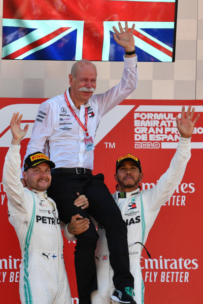 Valtteri Bottas, Mercedes AMG F1, 2nd position, and Lewis Hamilton, Mercedes AMG F1, 1st position, lift Dr Dieter Zetsche, CEO, Mercedes Benz, onto their shoulders on the podium