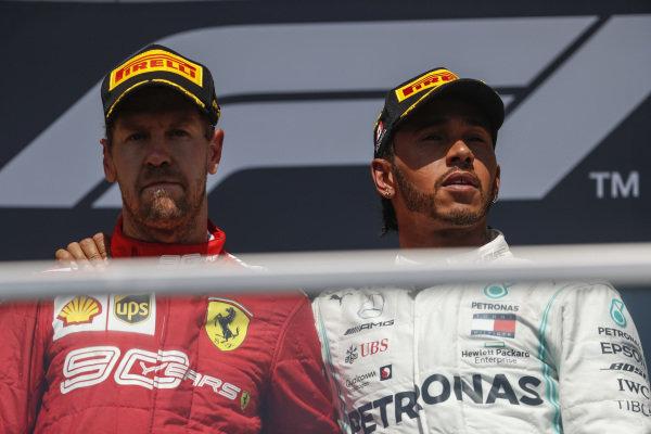Lewis Hamilton, Mercedes AMG F1 puts his arm around Sebastian Vettel, Ferrari on the podium