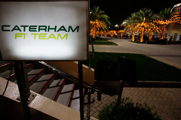 Bahrain International Circuit, Sakhir, Bahrain. Thursday 3 April 2014. The Caterham F1 logo in the paddock at night. World Copyright: Charles Coates/LAT Photographic. ref: Digital Image _N7T0579