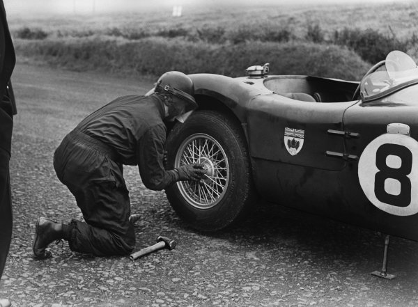 Dundrod, Great Britain. 5 September 1953.Peter Whitehead/an Stewart (Jaguar C-type), retired, wheel change with hammer, portrait. World Copyright: LAT Photographic.Ref:  B/W Print
