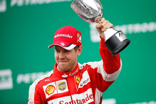 Interlagos, Sao Paulo, Brazil. Sunday 15 November 2015. Sebastian Vettel, Ferrari, 3rd Position, with his trophy on the podium. World Copyright: Charles Coates/LAT Photographic ref: Digital Image _J5R6583