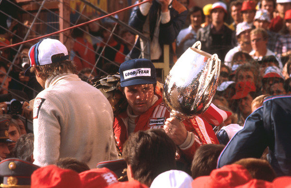 1977 Austrian Grand Prix.Osterreichring, Zeltweg, Austria.12-14 August 1977.Alan Jones (Shadow Ford) 1st position, takes his maiden Grand Prix win and the Shadow Racing Team's last. He celebrates on the podium with Hans-Joachim Stuck (Brabham Alfa Romeo) 3rd position, with his back towards us. Ref-77 AUT 09.World Copyright - LAT Photographic