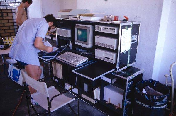 1987 Brazilian Grand Prix.Jacarepagua, Rio de Janeiro, Brazil.10-12 April 1987.Technicians in the back of the Team Lotus garage work on the telemtry system computer.Ref-87 BRA 03.World Copyright - LAT Photographic