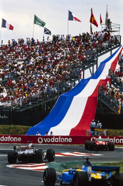 Michael Schumacher, Ferrari F2003-GA, leads David Coulthard, McLaren MP4-17D Mercedes, and Jarno Trulli, Renault R23.