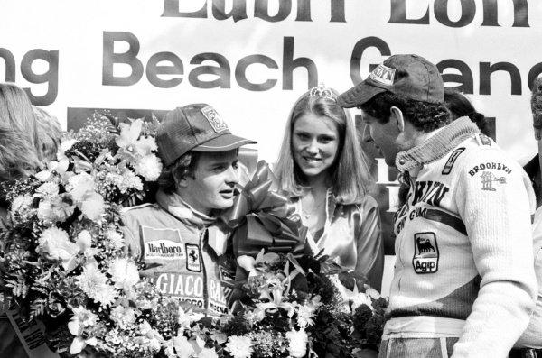 (L to R): Race winner Gilles Villeneuve (CDN) celebrates on the podium with his second placed Ferrari team mate Jody Scheckter (RSA).United States Grand Prix West, Rd 4, Long Beach, California, USA, 8 April 1979.