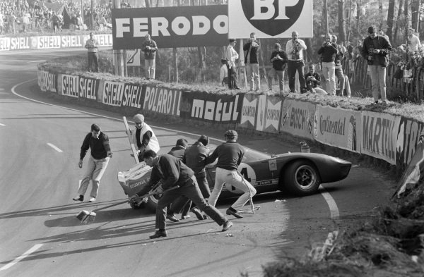 Marshals work to clear up and move the Ford GT40 of Peter Sutcliffe / Dieter Spoerry following an accident, as photographers take pictures.